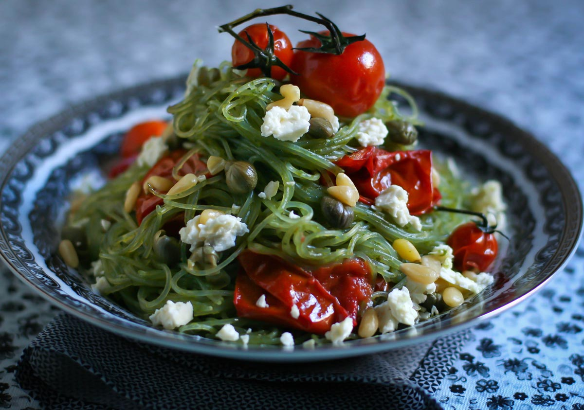 Pasta sin gluten: vermicelli de poroto mung, aceite de albahaca, tomates asados, alcaparras, piñones, queso feta